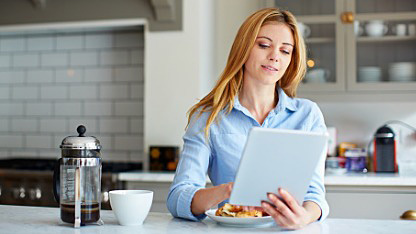 Woman in kitchen reading tablet
