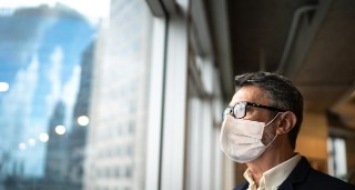 Man wearing mask looking out office window